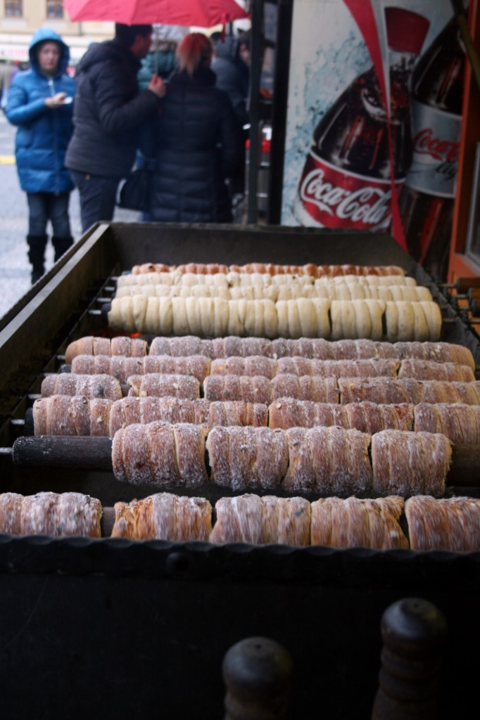 Trdelnik being baked over an open fire.  They pull it off the spindle and roll it again in sugar right when you buy it, making it warm and sugary sweet.